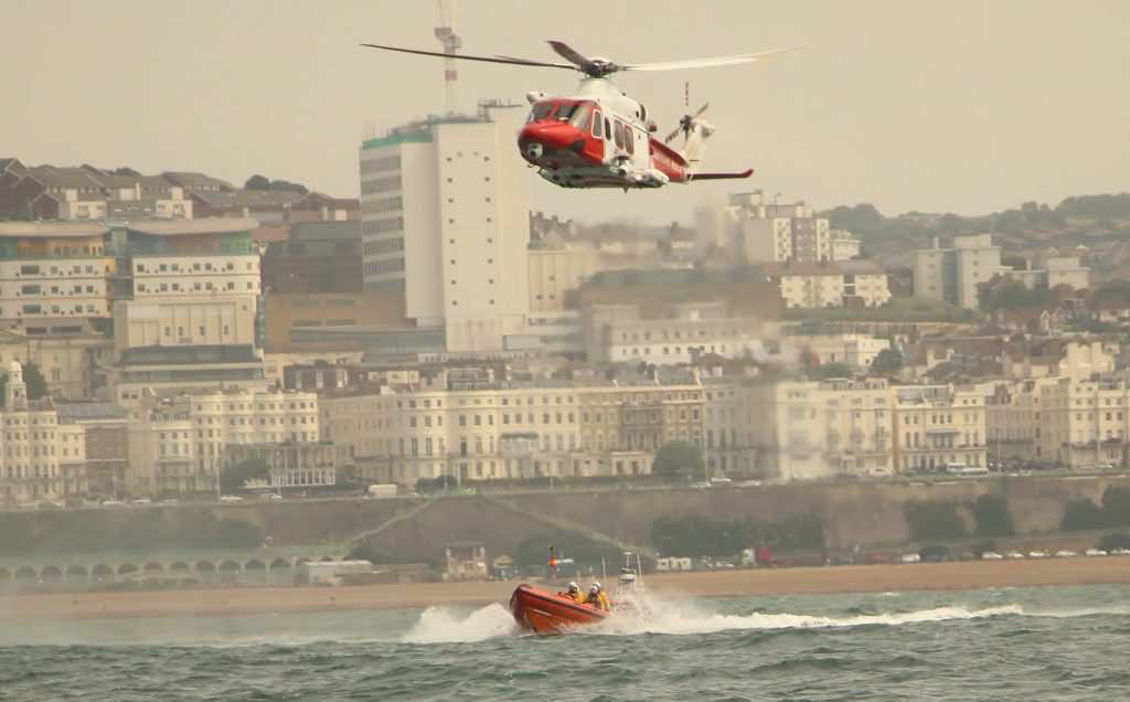 image of RNLI crew and helicopter practice nearby