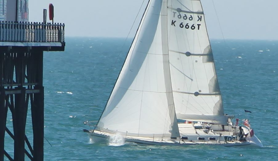 image of yacht passes close to pier