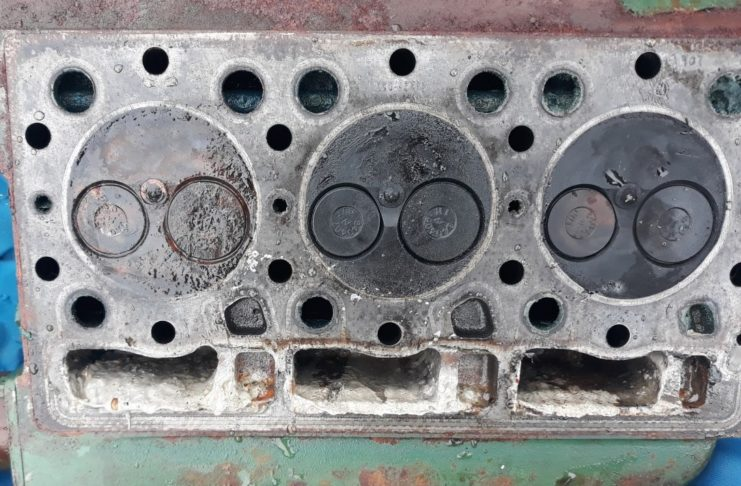 image of The underneath of the engine head showing the top of the three cylinders. Each has two valves-one opens to let air in and the other lets exhaust gases out. Seawater has got into the left hand one. Underneath there is a thick off white cream coloured mixture of oil and seawater.